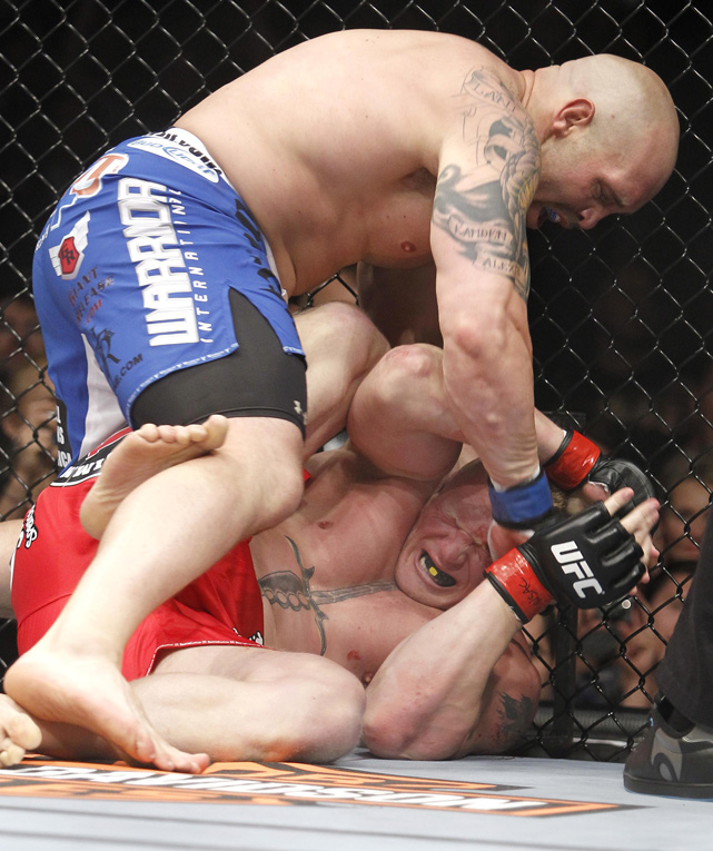 Lesnar gets punched in the head by Shane Carwin while defending his title at UFC 116 in July 2010. Lesnar would survive the attack and go on to win the fight by second-round submission.