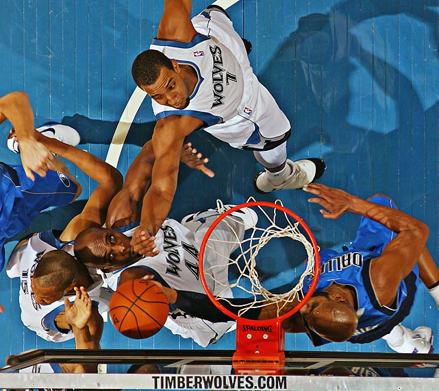 Vince Carter (right) of the Mavericks goes up for a layup against Anthony Tolliver and Derrick Williams of the Timberwolves.
