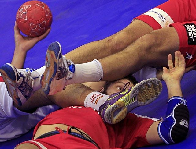 Iceland's Robert Gunnarson lies underneath a Spanish player during a main round match at the European Handball Championships.