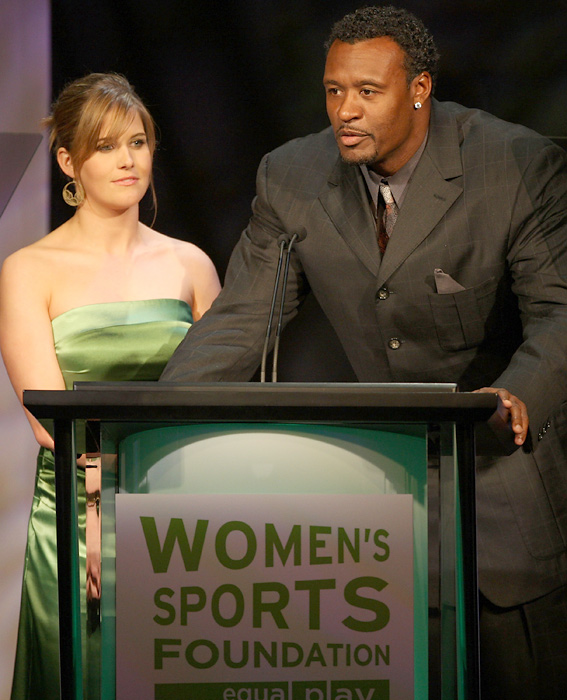 "Burke speaks on stage with former football player Willie McGinest at the Women's Sports Foundation's ""Billie Awards"" in Beverly Hills, Calif."