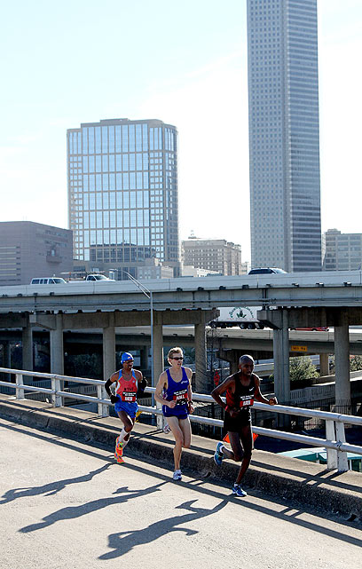 Meb Keflezighi (left), Ryan Hall (center) and Abdi Abdirahman follow the marathon route along a highway in Houston, Texas.