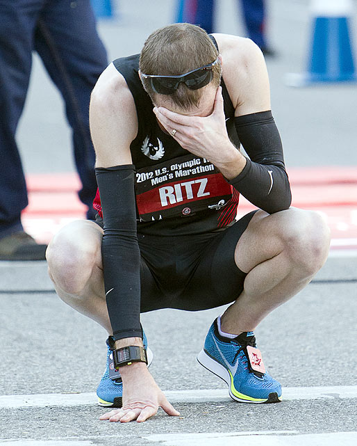 A dejected Dathan Ritzenhein collapses to his knees after finishing fourth and narrowly missing a chance to compete in the 2012 Games.