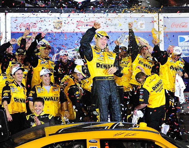 Matt Kenseth raises his fist in triumph with his crew after winning the 2009 race. Kenseth's win came after just 152 laps when a severe rainstorm forced the cancellation of the final 48. Kenseth took the lead just six laps before the race was stopped, getting his first win since November 2007.