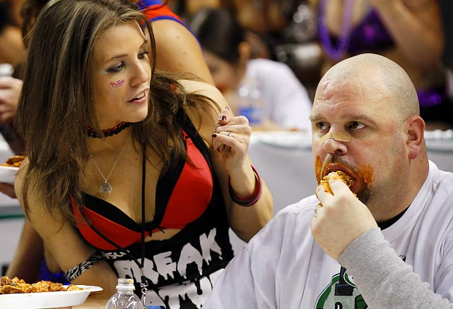 A Wingette holds a plate of wings for competitor John Harker. Wingettes, bikini- and lingerie-clad women who make up each eater's entourage, are a major Wing Bowl attraction.