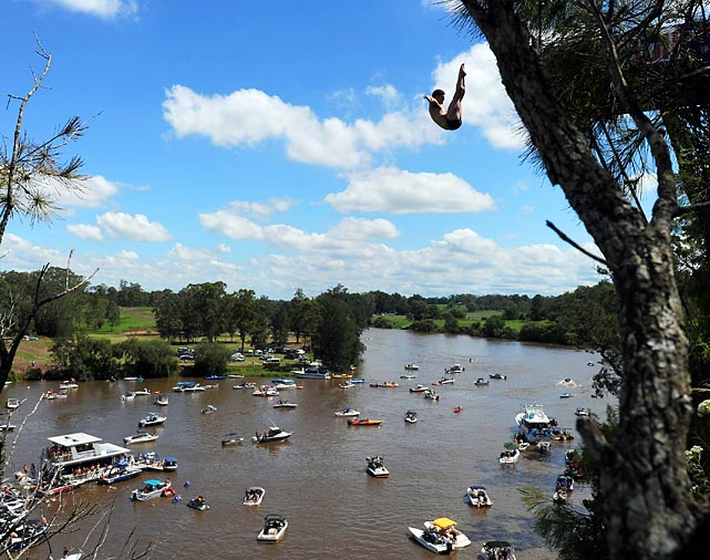 Spectators watch as a competitor dives from a 27.5 meter high platform in the Cliff Diving World Series qualification round in Sydney.