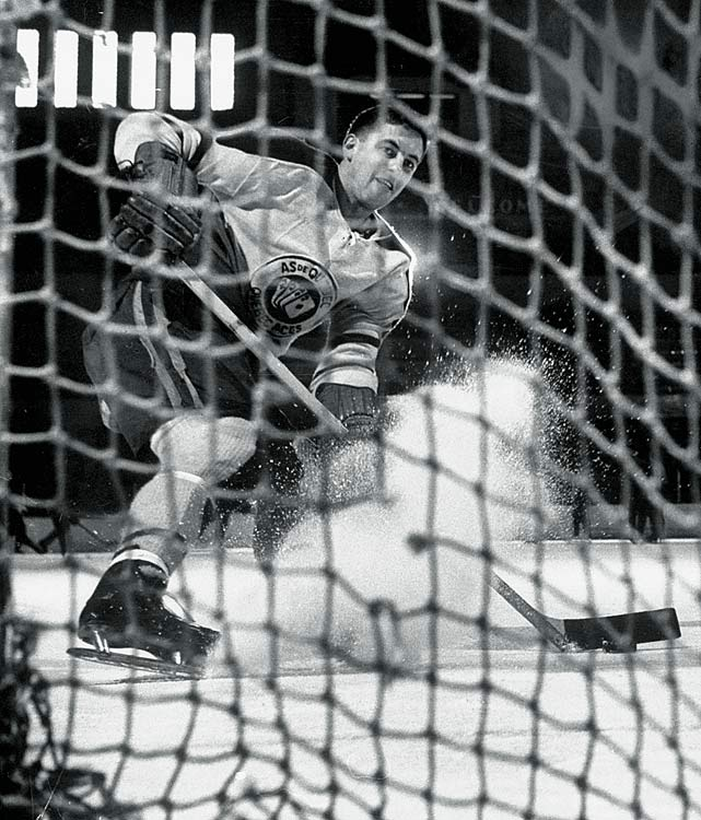 Jean Béliveau, playing with the Quebec Aces of the Quebec Senior Hockey League (QSHL), looks to shoot the puck into the net in Dec. 1952.