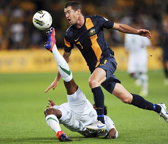 Australia's Brett Emerton tries to avoid being kicked in the face by Saudi Arabia's Kamil Saddiq Almousa in a World Cup Qualifier in Melbourne.