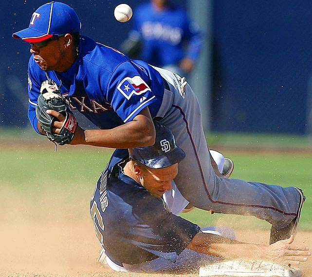 San Diego's Brad Davis slides into Texas second baseman Yangervis Solarte to break up a double play during a Spring Training game.
