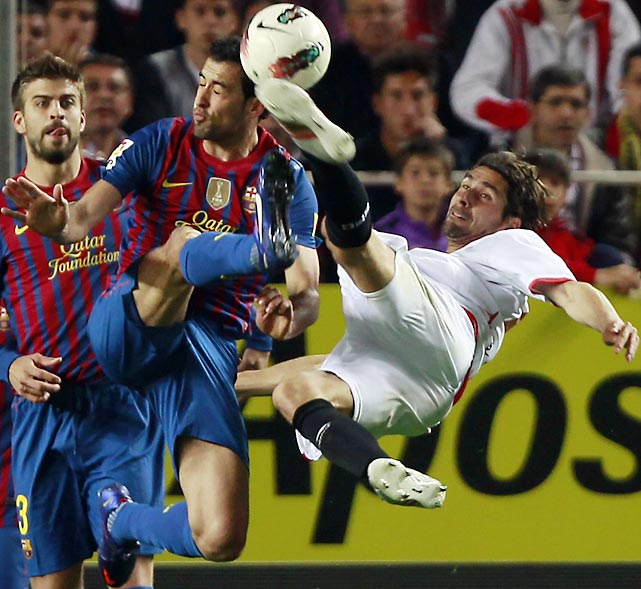 Barcelona's Sergio Busquets challenges Sevilla's Julien Escude during their Spanish First Division match in Seville.