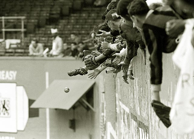 Fans reach out to try to catch a ball during an April 1963 Mets game at the Polo Grounds.