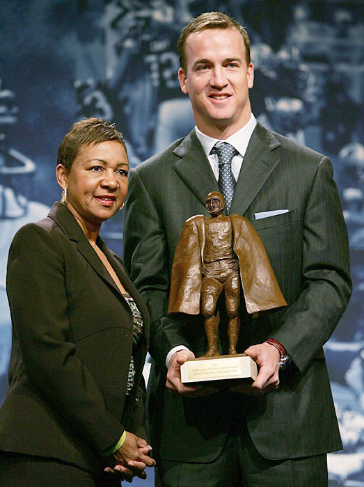Manning and Connie Payton hold the NFL's Walter Payton Man of the Year trophy at a press conference.