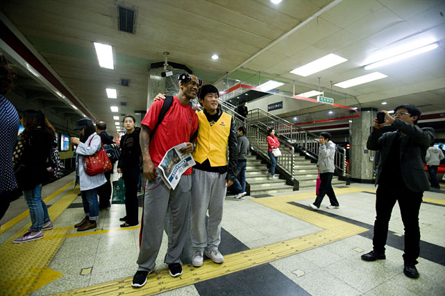 Marbury poses with a fan while waiting for the subway in Beijing.
