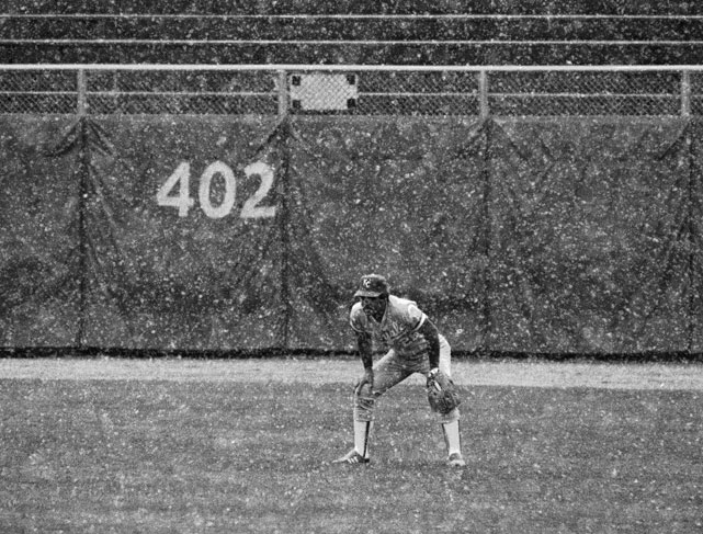 Kansas City's Amos Otis, almost obscured by snow, waits in centerfield during the first inning of a game against Milwaukee. Umpires eventually halted the action and called the contest as the snow continued to fall.