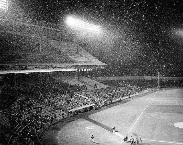 The Braves-Pirates baseball game is delayed by snow as the groundskeepers spread nylon covering over home plate. In spite of freezing temperature and snow a crowd of twelve thousand saw the game.