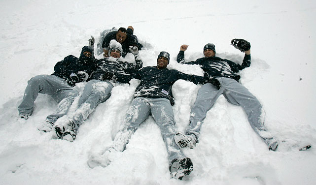 Jose Vidro (front), Jose Lopez, Adrian Beltre, and Richie Sexon lie in the snow at Jacobs Field before a game against the Indians.