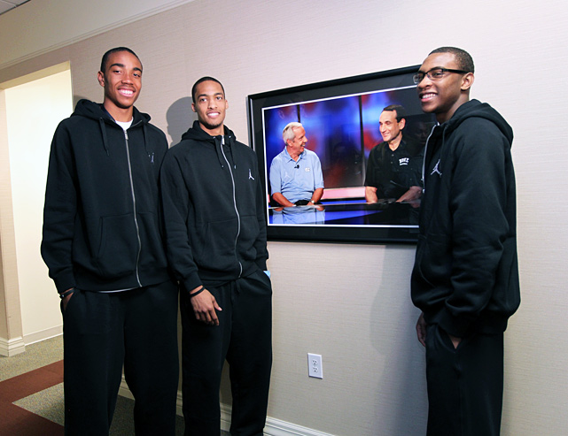 The next crop of recruits headed to Tobacco Road, Brice Johnson (left), Marcus Paige (middle) and Rasheed Sulaimon stand by a picture of their soon-to-be coaches. Johnson and Paige will suit up for UNC, while Sulaimon will play under Coach K at Duke.