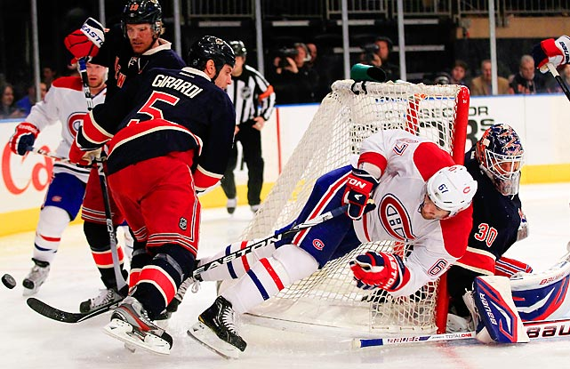 Dan Girardi of the Rangers knocks Max Pacioretty of the Canadiens into the net.