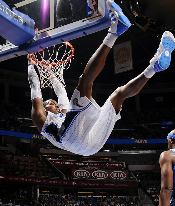 Dwight Howard hangs from the rim after dunking against the Dallas Mavericks.