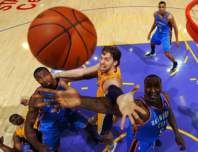 Laker's Pau Gasol tries to tip the ball towards the basket over the Thunder's Kendrick Perkins and Serge Ibaka.