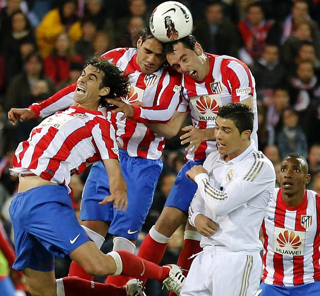 Atletico Madrid's players jump for the ball over Real Madrid forward Cristiano Ronaldo.