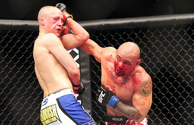 Eddie Yagin slugs fighter Mark Hominick during a featherweight bout at UFC 145 at Phillips Arena.