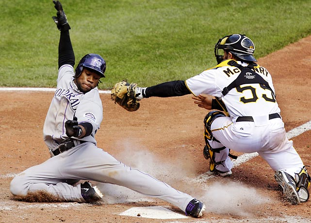 Eric Young Jr. avoids a tag by Pittsburgh's Michael McKenry in the eight inning of the Rockies 2-1 win.