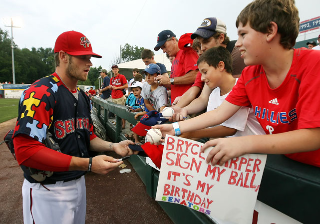 Midway through the 2011 season, Harper was promoted to the Double-A Harrisburg Senators. In this photo, he signs autographs for fans before a game against the Binghamton Mets at Metro Bank Park in Harrisburg, Penn.