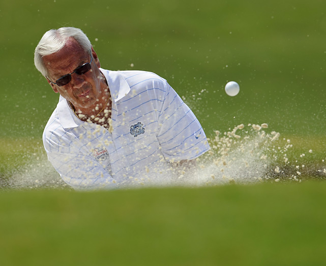 North Carolina basketball coach Roy Williams hits out of a sand trap.