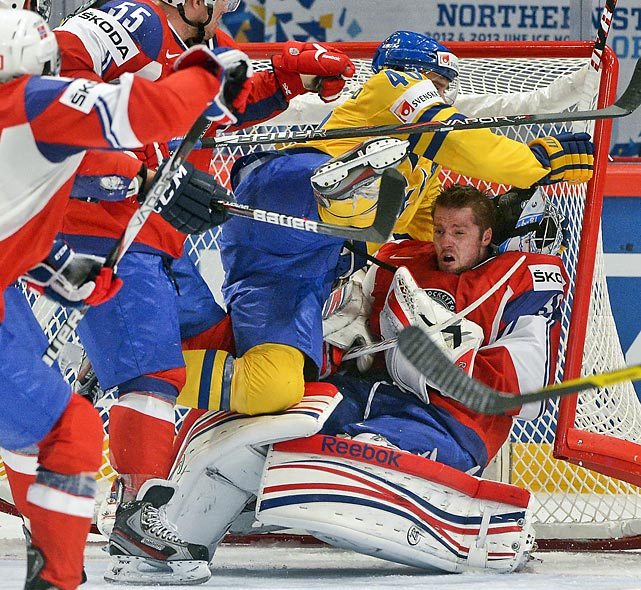 Norway's goaltender Lars Haugen loses his helmet as he's pushed into the goal by Sweden's Henrik Zetterberg during their Ice Hockey World Championship preliminary round match.