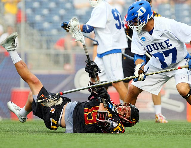 Maryland Terrapins midfielder Joe Cummings tries to pass from the ground around Duke defender Michael Manley during a semifinal of the NCAA lacrosse championships.