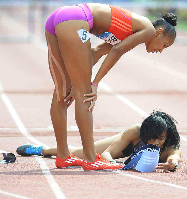 T'Erea Brown bends down to help her competitor Kaliese Spencer after the pair finished first and second, consecutively, in the women's 400 meter hurdles.