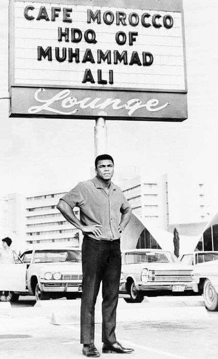 Muhammad Ali, fresh off changing his name from Cassius Clay after joining the Nation of Islam a year prior, stands before a sign denoting his training headquarters in Las Vegas, Nev., on Nov. 21, 1965. The following night, Ali successfully defended his heavyweight title against former two-time champion Floyd Patterson in a 12-round TKO.