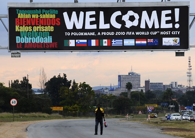 A South African man walks under a welcoming billboard in Polokwane, South Africa before the 2010 World Cup.