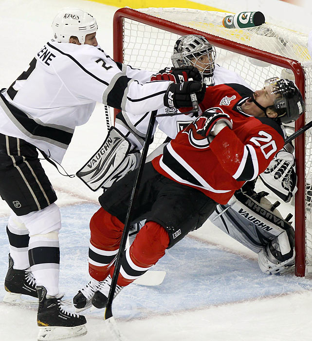 Kings' goalie Jonathan Quick keeps his focus even as teammate Matt Greene checks Ryan Carter of the Devils in front of the goal during Game 2 of the Stanley Cup Final.