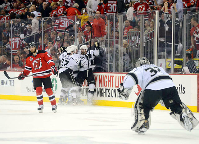Jonathan Quick (32) skates to join the celebration of Jeff Carter's overtime goal, which put the Kings up 2-0 in the Stanley Cup Finals.