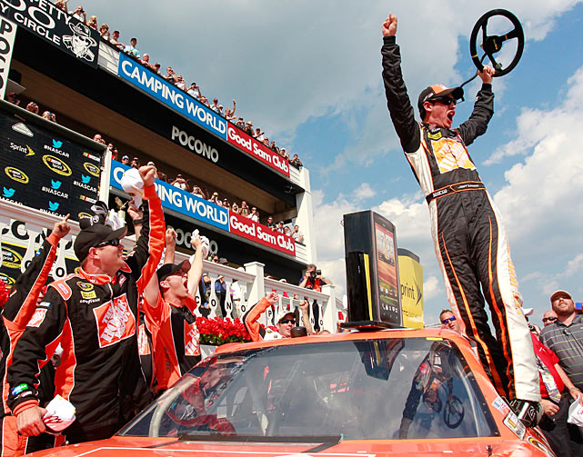 Steering wheel to the sky, Joey Logano celebrates victory at the NASCAR Sprint Cup Series Pocono 400 on top of his No. 20 Home Depot Toyota.