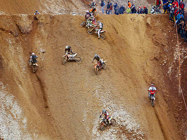 Motorcross riders slide down a hill in Eisenerz, a village in the Austrian province of Styria, during the Red Bull Hare Scramble, just one event of the Erzberg Rodeo.