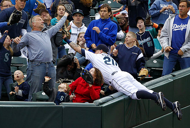 Seattle Mariners left fielder Mike Carp goes flying into the stands only to lose the ball to a home fan. The Mariners would lose the game, too, 8-3 to the Los Angeles Dodgers.