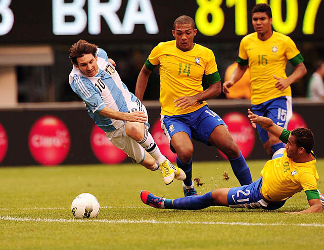 Lionel Messi gets slide tackled just outside of the 18-yard box by Brazilian defender Danilo.  Messi had a hat-trick, including the winning goal for Argentina in the 4-3 victory.