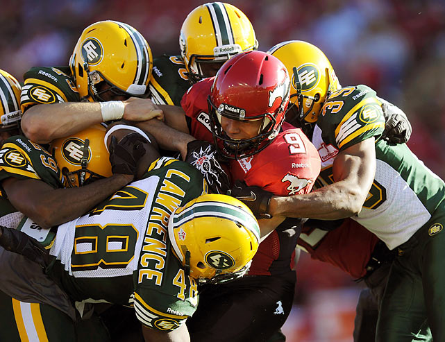 Jon Cornish of the Calgary Stampeders gets gang-tackled by a pile of Edmonton Eskimos during their preseason CFL game in Calgary, Alberta.