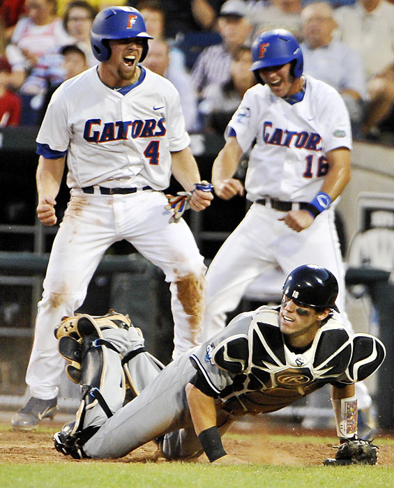 Nolan Fontana (4) and Justin Shafer of Florida celebrate after scoring on a double in the third inning of the College World Series.  Catcher Dante Rosenberg and his South Carolina teammates would have the final celebration after a 7-3 victory.