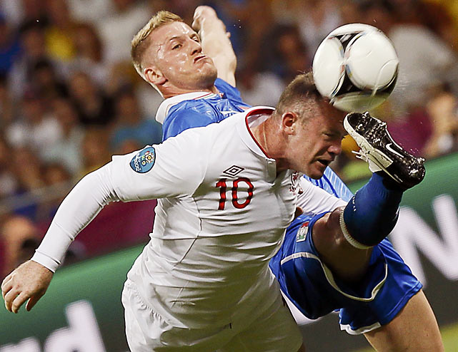 England's Wayne Rooney tries to get his head on the ball but was denied by the foot of Italy's Ignazio Abate.