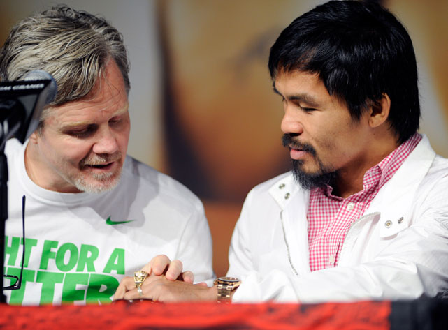 Roach, a five-time Trainer of the Year, checks out his fighter's new piece of jewelry.