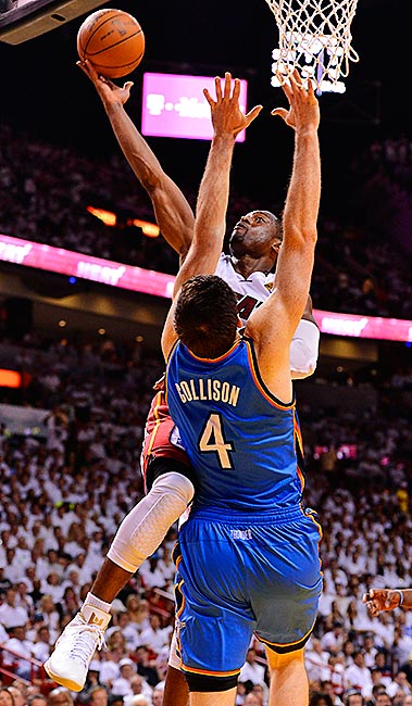 Nick Collison tries to defend a shot by Dwyane Wade.