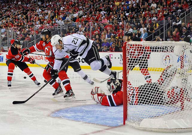 Dustin Brown of the Kings is sent flying in front of Martin Brodeur's net during the first minute of play.