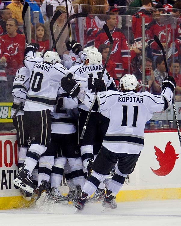 Kings center Jeff Carter is surrounded by teammates after his overtime goal sealed the 2-1 win, giving Los Angeles a 2-0 series lead.