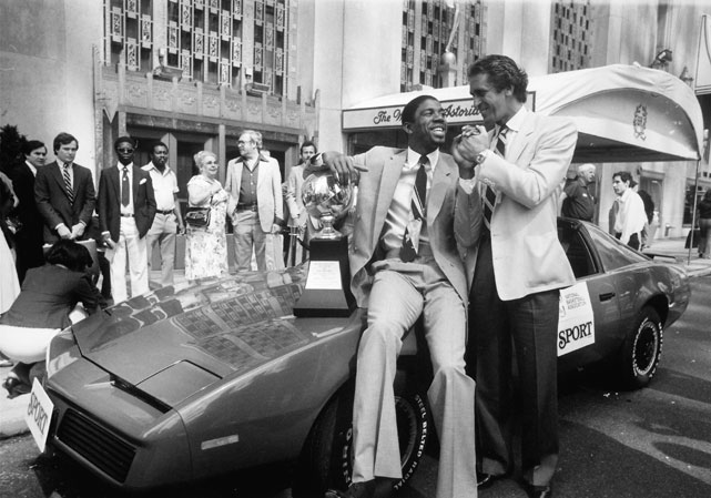 Riley shakes hands with Magic Johnson after Johnson was awarded a car and a trophy for winning MVP of the 1982 NBA Finals.