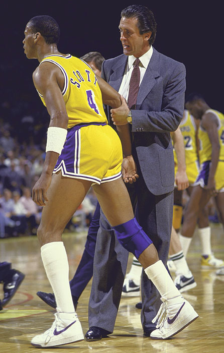 Riley holds back Lakers point guard and future NBA coach Byron Scott during a 1986 regular season game.
