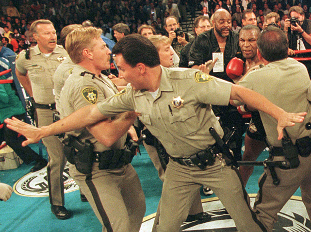 Tyson takes a swing at a Las Vegas policeman during the postfight melee.