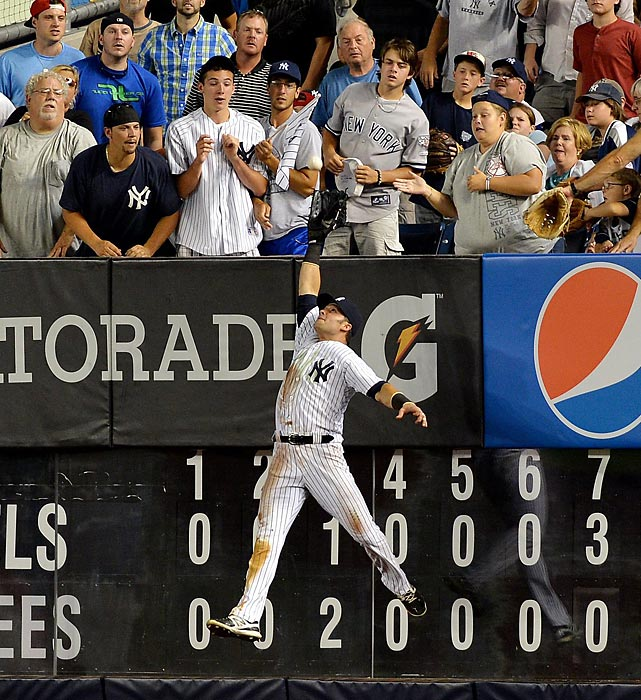 Fans look on as Nick Swisher of the Yankees prepares to catch a would-be home-run ball by the Angels' Mark Trumbo. The Yankees went on to defeat the Angels 6-5 at Yankee Stadium on July 13.